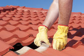 Construction worker tile roofing repair — ストック写真