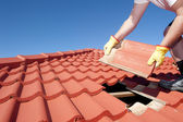 Construction worker tile roofing repairs — Stock fotografie