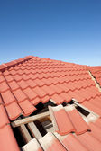 Damaged red tile roof construction house — Stock Photo