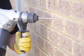 Hand holding drill at wall — Stock Photo