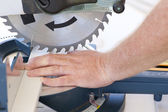 Safety at workplace with circular saw and hand — Stock Photo