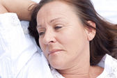 Sad contemplating mature woman resting in bed — Stock Photo