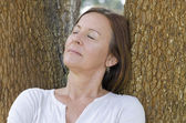 Mature woman relaxed closed eyes outdoor — Stock Photo