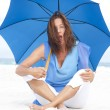 Surprised Mature woman blue umbrella beach — Stock Photo #22955058
