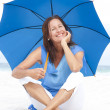Happy Mature woman blue umbrella beach — Stock Photo #22955062