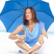 Worried Mature woman blue umbrella beach — Stock Photo #22955068