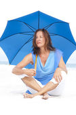 Worried Mature woman blue umbrella beach — Stock Photo