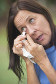 Sad mature woman tissue cleaning tears in eye — Stock Photo