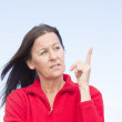 Thinking woman with finger up — Stock Photo