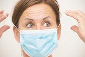 Vrouwelijke verpleegkundige of arts met masker over gezicht — Stockfoto
