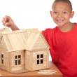 Boy builds popsicle house — Stock Photo