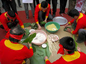 People in traditional costume exam to make square glutinous rice — Stock Photo