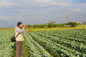 Reporter take photo in the field — Stock Photo
