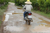 The unidentified man rides motorcycle on muddy road — Stock Photo