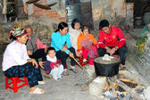 A family sitting inside the pot spoke the traditional rice cake — Stock Photo