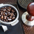 Espresso filter filled with coffee beans and tamper — Stock Photo #38324713