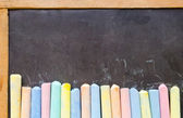 Colorful chalks on blackboard — Stockfoto