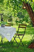Entorno idílico de una pequeña mesa de centro y silla de madera — Foto de Stock