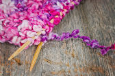 Colorful knitting and wooden needles on rustic background — Stock Photo