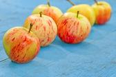 красные яблоки на синем фоне деревенском — Стоковое фото