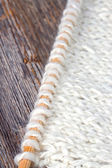 White knitting and needle on rustic wooden background — Stock Photo