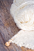White knitting on rustic wooden background — Stock Photo