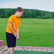 Boy playing golf in the summer — Stock Photo