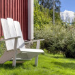 White lawn chair in summer garden — Stock Photo