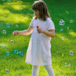 Young girl playing with soap bubbles — Stock Photo