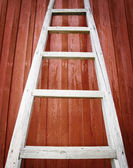 Rustic wooden ladder on red background — Stock fotografie