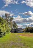 Old barn with blue sky and clouds — Stock Photo