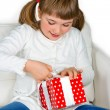 Stock Photo: Happy little girl opening a present