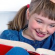 Stock Photo: Little girl smiling and reading a book