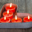 Red candles on a heart shaped tin tray — Stock fotografie