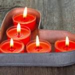 Красные свечи на сердце формы олова лоток — Стоковое фото