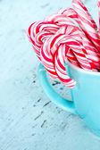 Bastones de caramelo en una taza de la luz azul — Foto de Stock