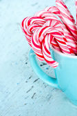 Candy canes in a light blue cup — Stock Photo