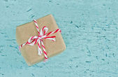 Gift box wrapped in brown paper with red striped string — Stock Photo