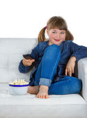 Girl sitting on a couch watching TV — Stock Photo