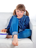 Pretty little girl sitting on a couch — Stock Photo
