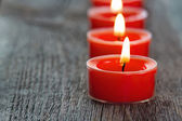 Red burning candles on a wooden background — Stock Photo