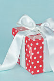 Red polkadot gift box with white bow — Stock Photo