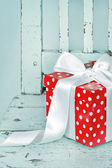 Red gift box with white bow — Stock Photo