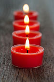 Red burning candles on a wooden rustic background — Stock Photo