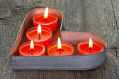 Red candles on a heart shaped tin tray — Stock Photo