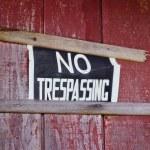 No trespassing sign nailed to house exterior — Stock Photo #15532007