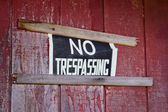 No trespassing sign nailed to house exterior — Stock Photo