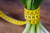 Green onions with yellow measurement tape — Stock Photo