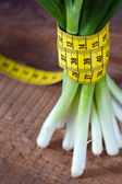 Onion stems and measurement tape — Stock Photo