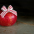 Red apple with Christmas bow on dark background — Stock Photo